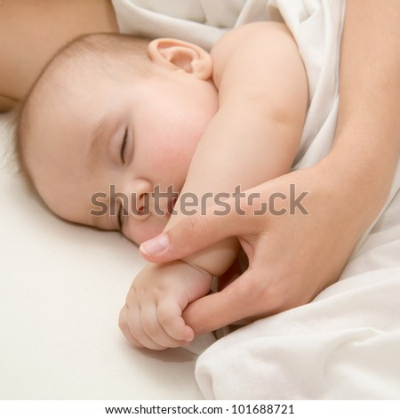 Sleeping newborn baby covered with white woolen blanket in bed.