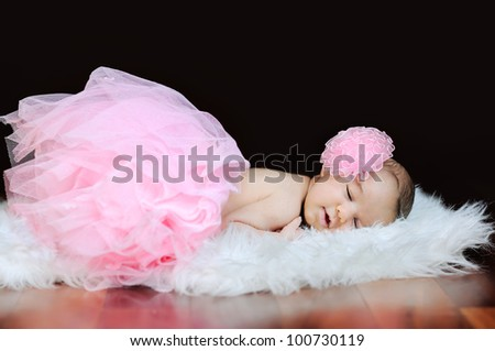Sleeping newborn baby dressed in pink tutu skirt