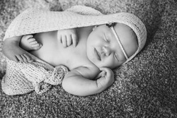 Sleeping newborn baby girl. Baby girl lies wrapped in a beige knit fabric.