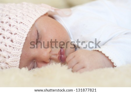 Sleeping newborn baby girl in pink hat  on fur.