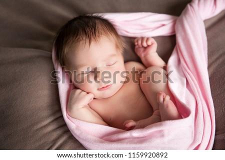 Sleeping newborn baby girl. Newborn child embryo, fetus, impregnation, birth, new life, IVF concept. Newborn baby wrapped in a pink fabric, lies on a soft blanket