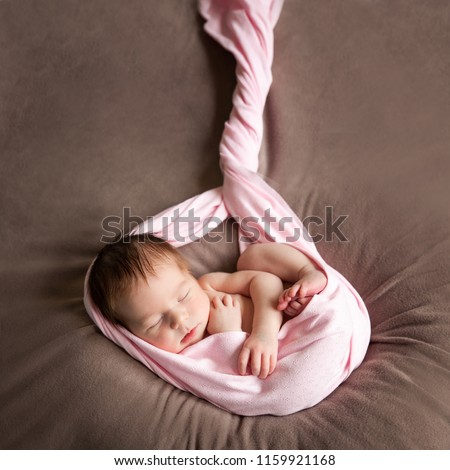 Sleeping newborn baby girl. Newborn child embryo, fetus, impregnation, birth, new life, IVF concept. Newborn baby wrapped in a pink fabric, lies on a soft blanket