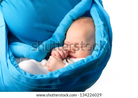 Sleeping newborn baby in a sling, isolated on white