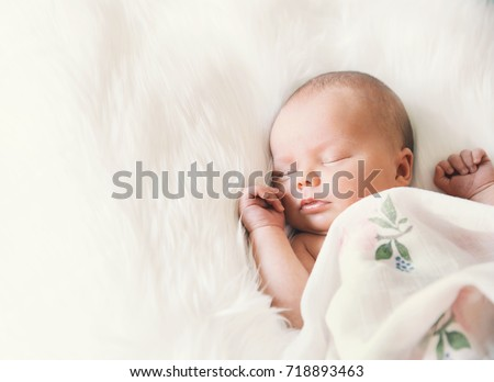 Stock Photo Sleeping newborn baby in a wrap on white blanket. Beautiful portrait of little child girl 7 days, one week old.