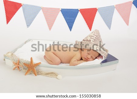 Sleeping newborn baby in tiny wooden boat prop with sailors hat