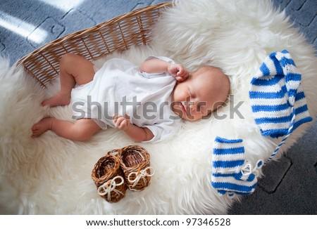 Sleeping newborn baby in wicker basket lying on sheepskin
