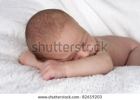 sleeping newborn baby resting head on arms