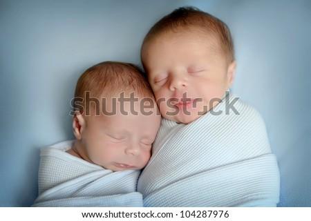 sleeping newborn twins, on blue blanket