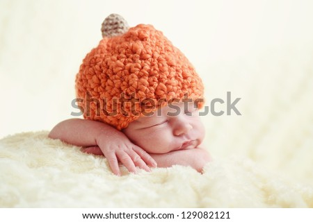 sleeping newborn wearing pumpkin hat