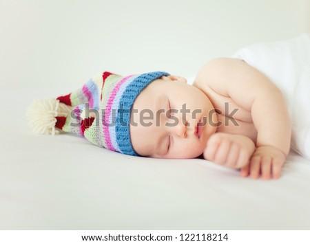 sleeping sweet baby wearing funny striped hat