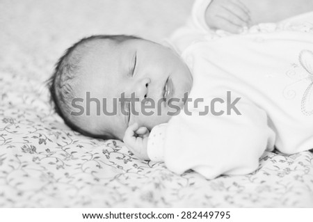 sleeping sweet newborn girl on the bed