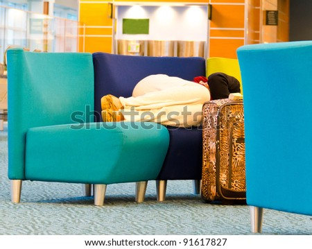 Sleeping woman (passenger) in the airport terminal  in anticipation of departure (landing) of an aircraft (or any transport). Flight delay due to weather or strike.