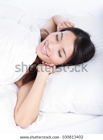 Sleeping woman wake up in the morning lying on bed at home, model is a asian girl