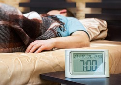 Sleeping young man with alarm clock at foreground