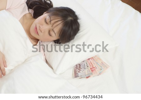 Sleeping young woman with New Taiwan Dollars