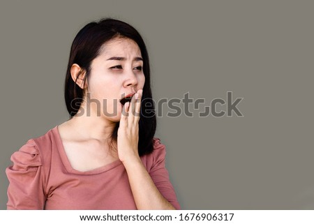 sleepless Asian woman yawning and tired from insomnia with dark eyes circle