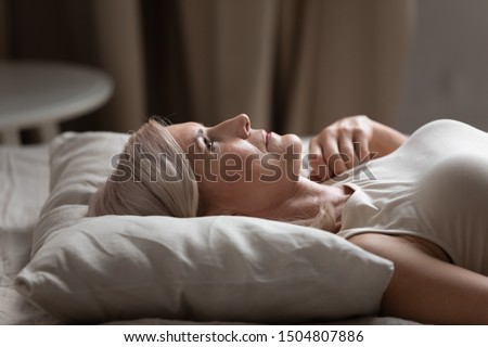 Sleepless mature woman with open eyes lying on soft pillow close up, suffering from insomnia, lack of sleep, older female lying in bed in the morning, looking up, thinking, early awakening