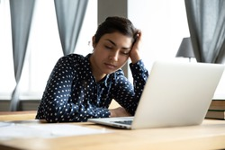 Sleepy indian ethnicity businesswoman fall asleep seated at workplace desk near laptop. Boring job and lack of sleep, unmotivated employee feels disinterested, overworked woman stressful work concept