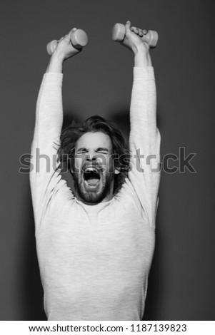 sleepy man with barbell or dumbbell workout, has disheveled and uncombed long hair and beard on yawning face in white underwear on blue background, morning exercise and wake up, barbershop, sport