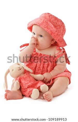 Sleepy 6 month old baby girl sits sucking her thumb and holds a stuffed toy bunny rabbit. Baby's strawberry pink floral hat and sun dress match the toy. Vertical, copy space, isolated on white.