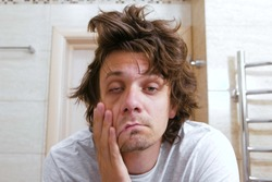 Sleepy shaggy young man looks at the mirror in bathroom in the morning.