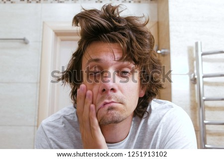 Sleepy shaggy young man looks at the mirror in bathroom in the morning. Stock photo ©