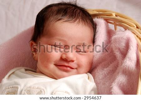 sleepy, smiling baby in basket