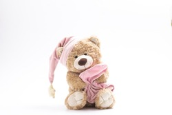 Sleepy soft toy bear in a cap with a pink blanket on a white background. The concept of childhood, sleep, falling asleep, dreams. Isolated. Horizontal.