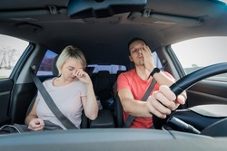 Sleepy tired man and woman fall asleep driving car at speed. Yawning of driver wearing sefaty belt in traffic jam. Unsafe road trip.
