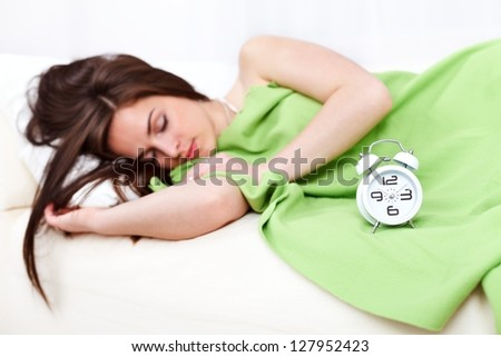 Sleepy woman lying in bed with alarm clock in front