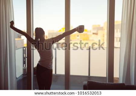 Stock Photo Sleepy woman stretching,drinking a coffee to wake up early in the monday morning sunrise.Starting your day.Wellbeing.Positive energy,productivity,happiness,enjoyment concept.Morning ritual