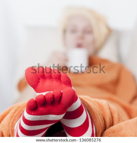 sleepy women lying on sofa drinking hot beverage