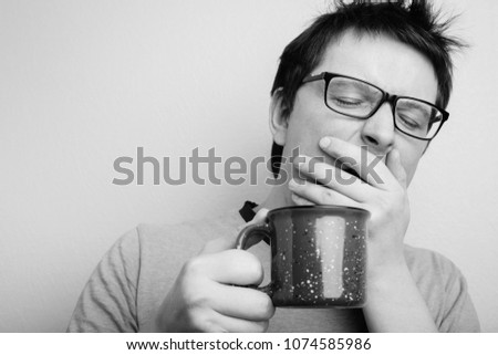 Sleepy yawning man in eyeglasses with red cup of tea or coffee has uncombed hair in underwear on light background, morning refreshment and drink. Copy space for your text. black and white photo. ストックフォト ©