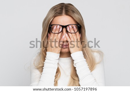 Sleepy young caucasian businesswoman in eyeglasses rubbing her eyes, feels tired after working on laptop, isolated on grey background.Overwork, tired, health concept.Exhausted, fatigue eyes