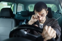 Sleepy young man rubs his eyes with his right hand. His left hand is on the steering wheel. He is sitting at his car. Road safety concept.
