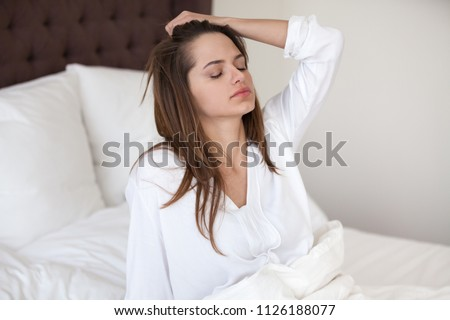 Sleepy young woman feeling drowsy or dizzy after waking up in bed, suffering from lack of sleep deprivation, insomnia, morning headache or migraine, having hangover after sleepless night concept Stock photo ©