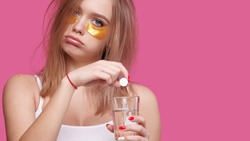Sleepy young woman with patches under the eyes puts pain relieving tablet into glass of water. Girl after hangover early in the morning, pink isolated background
