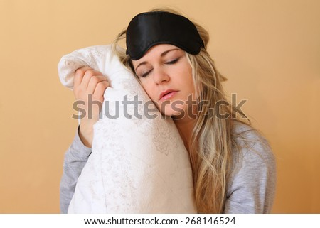 Sleepy young women with pillow and sleeping eye mask still on.