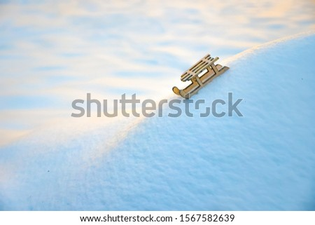 Sleigh on snow for greeting card. Wooden sleigh on white snow. Toy of sleigh on snow hill. Copy space. Greeting card for winter holiday. Symbol of new year. Greeting card, brochure. Background of snow