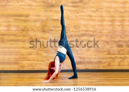 Slender athletic girl on the background of wood rooms in Standing Split yoga pose, Urdhva Prasarita Eka Padasana, stretching exercise - Picture