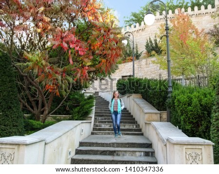 Slender blonde girl descends the stairs against of a copy of the wall of Baku fortress and oriental plants in Heydar Aliyev Park in Kiev (Ukraine). Concept of a happy tourist in a beautiful cityscape