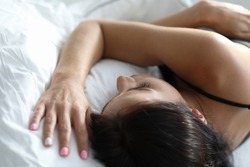 Slender brunette girl resting on white bedding. Pillows are not very soft and large. Relaxation and speedy falling asleep. It necessary to relax muscles. Strategies for controlling negative thoughts