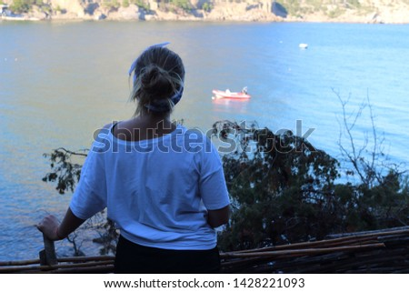 Slender girl in a white T-shirt on the background of the Crimean Mountains on the Black Sea coast looks at the beautiful landscape. Crimea, Russia