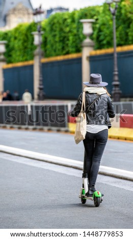 Slender girl in stylish fashionable clothes with a bag on her shoulder and a felt hat traveling the streets of the city driving on an electric scooter to have time to visit more famous places #1448779853