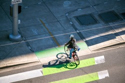 Slender girl on a bike rides across the road along green lane for cyclists allocated at the pedestrian crossing preferring an active healthy lifestyle using cycling as an alternative transportation