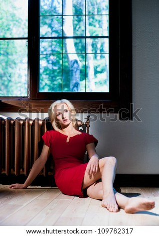 Slender girl sitting by the window