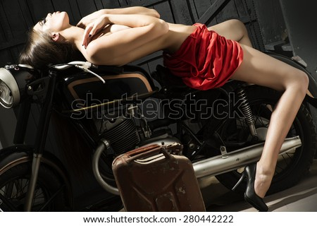 Slender sexual young woman with bright make up in flat red dress and black lingerie sitting on old motorbike in garage in sexy pose on workshop background, horizontal picture
