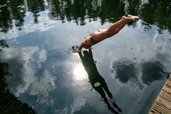 Slender woman jumping with a wooden bridge and dives headfirst into the clear lake, with a smooth and calm water, which can be seen in its reflection. Tourist life. Active summer holiday.