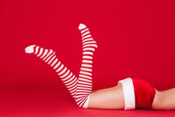 slender woman legs in striped Christmas stockings on a red background