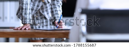 Slender woman stands in office and signs document. Employee training, continuing education. Professional career, growth and promotion. Convey to others your words and emotions. Work subordinates Foto stock ©